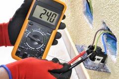 Elektrikertekniker på arbete med säkerhetsutrustning på ett bostads- elektriskt system royaltyfri foto