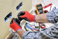Elektrikertekniker på arbete med säkerhetsutrustning på ett bostads- elektriskt system royaltyfria bilder