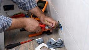 Elektrikertekniker p? arbete p? ett bostads- elektriskt system Konstruktionsbransch arkivfilmer