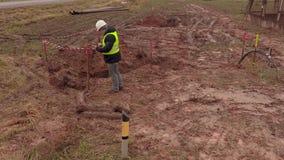 Elektrikerteknikerkontroll utgrävninggropen för elektriska kablar arkivfilmer
