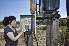 Elektrikerteknikerkvinna som kontrollerar elmätaren och invo Arkivfoton