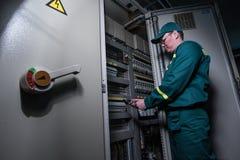 Elektrikerteknikern testar elektrisk utrustning på en stor växt arkivfoto