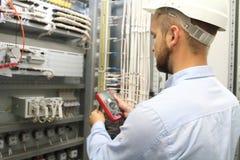Elektrikerteknikern testar elektriska installationer och trådar royaltyfri fotografi