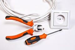 Elektrikerwerkzeuge, -kabel und -Wandsteckdose Stockfoto