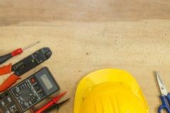 Elektrikerwerkzeuge, -komponenten und -instrumente auf einem hölzernen Hintergrund stockbild