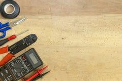 Elektrikerwerkzeuge, -komponenten und -instrumente auf einem hölzernen Hintergrund stockfoto