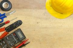 Elektrikerwerkzeuge, -komponenten und -instrumente auf einem hölzernen Hintergrund lizenzfreies stockbild
