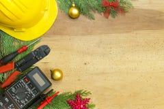 Elektrikerwerkzeuge und Instrumente und Weihnachtsdekorationen auf hölzernem Hintergrund stockfotos