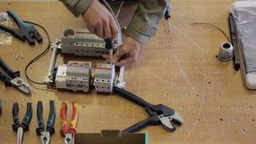 Elektrisch op Desktop maakt de schroevedraaier een draad aan het schakelbord vast stock video