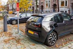 Elektrische aandrijvingsauto die op straat in Amsterdam, Nederland laden Stock Fotografie