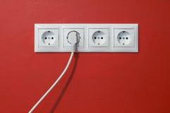Elektrische Anschlüsse, Seilzug und elektrischer Bolzen auf Rot stockbilder