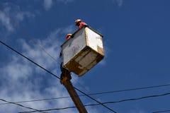 Elektrische Arbeitskräfte auf Telehandler mit dem Eimer, der Hochspannungsdrähte auf hohe Betonpfosten Unterseite installiert, se lizenzfreies stockbild