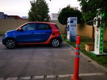 Elektrische auto die in aan elektriciteit wordt gestopt die - een elektrische auto laadt stock afbeelding