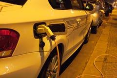 Elektrische auto's die bij nacht in stadsstraat laden Stock Foto