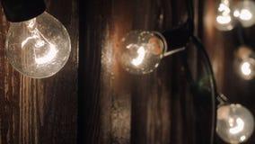 Elektrische Birnen werden in einer Girlande draußen nachts angeschlossen stock footage