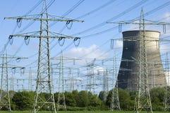 Elektrische centrale en elektriciteitspylonen tussen bomen Stock Foto