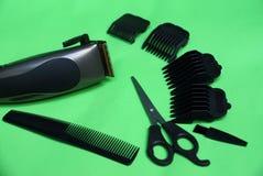Elektrische clipper en een reeks toebehoren van schaar, kammen en zwarte gehechtheid op een groene lijst stock foto's