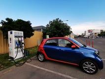 Elektrische die auto in aan elektriciteit wordt gestopt die - een elektrische auto laden royalty-vrije stock afbeelding