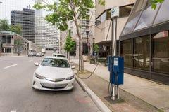 Elektrische die auto in een EV-het laden post wordt gestopt stock foto