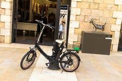 Elektrische fiets dichtbij open deur van winkel bij Mamilla-Straat in Jeruzalem Royalty-vrije Stock Foto's
