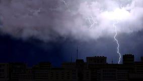 Elektrische firebolts, die von Wolken zu Boden in der Nachtstadt, schlechtes Wetter schlagen Lizenzfreie Stockfotos