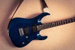 Elektrische gitaar op een achtergrond van uitstekende beige muur Stock Foto