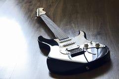 Elektrische gitaar UCLA, die op de vloer en de wachtende musicus liggen Royalty-vrije Stock Foto's
