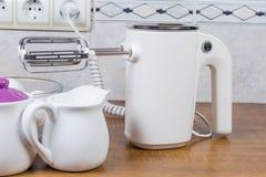 Elektrische handbediende mixer tegen van verschillend aardewerk op lijst stock afbeeldingen