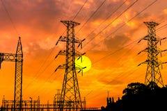 Elektrische Hochspannungssäulen des Schattenbildes auf Sonnenunterganghintergrund Stockfoto