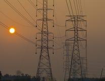 Elektrische Hochspannungstürme Silhoutte bei Sonnenuntergang. Stockbild