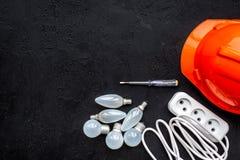 Elektrische Installation, Arbeitskonzept verdrahtend Schutzhelm, Birne, Sockelausgang auf schwarzem Draufsicht-Kopienraum des Hin Stockbild