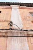Elektrische keramische Sicherungen und schwarze Drähte unter Schieferdach auf horizontaler Wand der rosa schäbigen Farbe lizenzfreie stockfotos