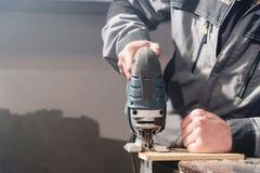 Elektrische Laubsäge der Nahaufnahme in den Händen einer Arbeitskraft in einer Hauptwerkstatt Beginnen eines Geschäfts handwerker stockfotos