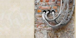 Elektrische Leistung und Telefonkabel gegen eine Ziegelstein- und Gipswand - Bild mit Kopienraum lizenzfreies stockfoto