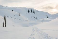 Elektrische Linie, die einen Weg im Schnee kreuzt Stockbild