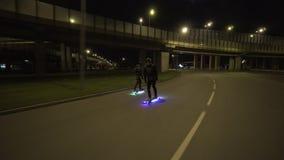 Elektrische Longboard-Fahrt in der Nachtstadt mit geführt und Motoren stock video