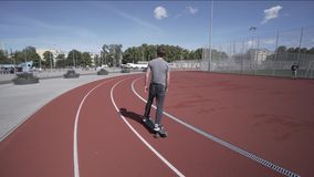 Elektrische Longboard-Sommerfahrt auf rotes Sportstadion mit Spielplatz stock footage