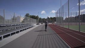 Elektrische Longboard-Sommerfahrt auf rotes Sportstadion mit Spielplatz stock video footage