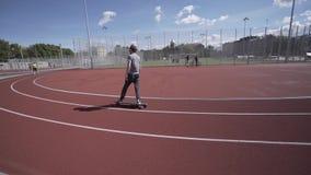 Elektrische Longboard-Sommerfahrt auf rotes Sportstadion mit Spielplatz stock video