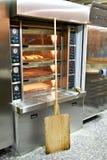 Elektrische oven in bakkerij en houten spatel voor ladingsbrood Stock Afbeeldingen