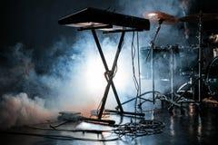 Elektrische piano en trommeluitrusting in donkere rokerige studio Royalty-vrije Stock Fotografie