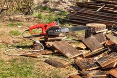 Elektrische Sägen und Kettensäge Elektrisch sah Kette auf dem Hintergrund des Schnittholzes Das Konzept der Verarbeitung des Holz lizenzfreie stockbilder