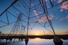 Elektrische Türme mit Leitlinien bei Sonnenuntergang, mit Reflexionen im Wasser stockbild