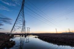 Elektrische Türme mit Leitlinien bei Sonnenuntergang, mit Reflexionen im Wasser stockfotos