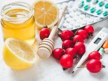 Elektrische thermometer, pillen, verse gele citroen, bank met honing royalty-vrije stock foto