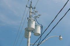 elektrische Transformatoren, die am hellen Pfosten gegen dunkelblauen Himmel hängen Lizenzfreies Stockfoto