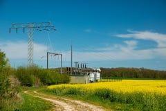Elektrische Transformatorstation steht auf einem Canolafeld stockfoto