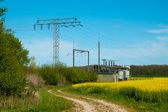 Elektrische Transformatorstation steht auf einem Canolafeld lizenzfreie stockbilder