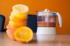 Elektrischer Juicer voll des frischen Zitrusfruchtsafts mit einem Stapel von zusammengedrückten Zitrusfrüchten unscharf Stockfotografie