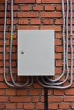 Elektrischer Kasten auf einer Backsteinmauer Plastikkabelkanäle stockfotografie